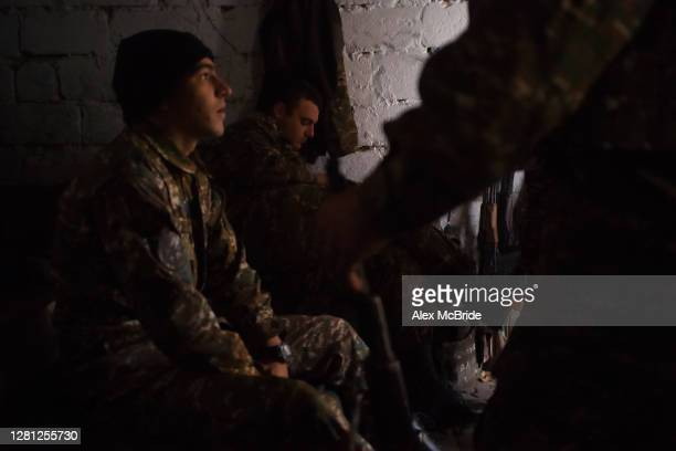 Armenian soldiers take cover in a bunker on the frontline as a UAV drone is heard flying overhead on October 20, 2020 near Aghdam, Nagorno-Karabakh....