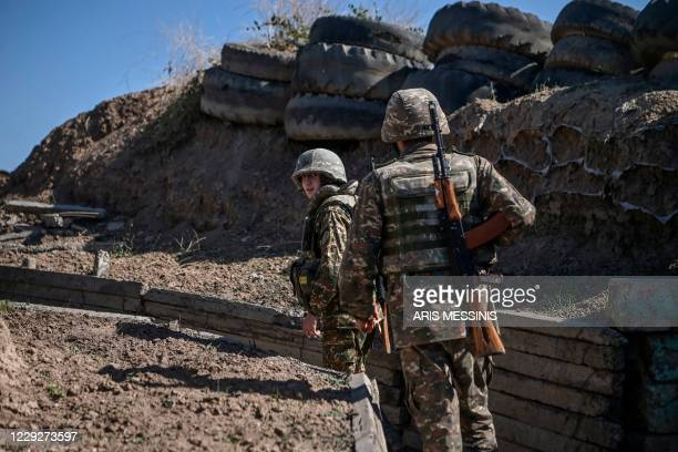 Armenian soldiers walk as troops hold positions on the front line on October 25 during the ongoing fighting between Armenian and Azerbaijani forces...