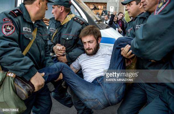 Armenian special police forces detain an opposition supporter during an antigovernment rally in front of the entrance of the government headquarters...