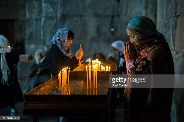 armenian woman praying at tatev monastery in armenia - armenia stock pictures, royalty-free photos & images