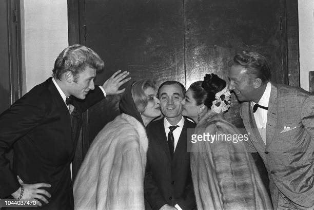 Armenianborn French singer Charles Aznavour is congratulated by singer Johnny Hallyday Greek actress and singer Melina Mercouri flamenco dancer La...