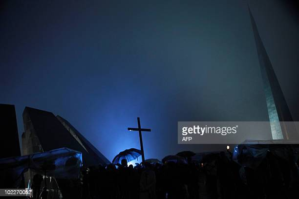 Armenians hold a cross in Yerevan early morning on April 24 2010 as they rally to mark the 95th anniversary of the 1915 mass killing of Armenians in...