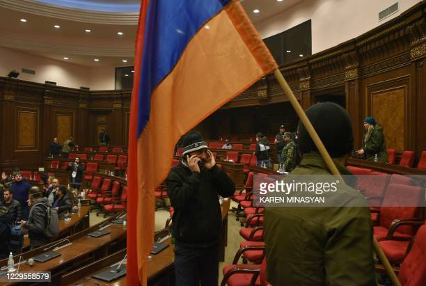 Armenians protest against the country's agreement to end fighting with Azerbaijan over the disputed Nagorno-Karabakh region inside the parliament in...