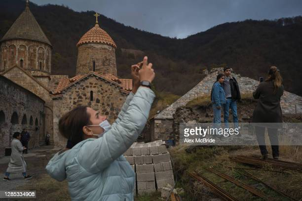 Armenians take pictures outside the 9th Century Dadivank Monestery as fear of Azeri persecution prompts them to abandon the monestary on November 12,...