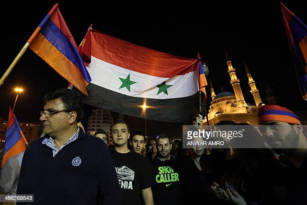 Armenians wave their national flag alongside the Syrian flag during a gathering to commemorate the 99th anniversary of the Ottoman Turkish genocide...