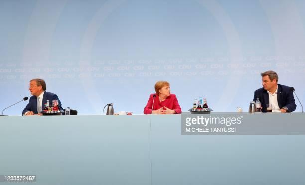 Armin Laschet, leader of the Christian Democratic Union party, German Chancellor Angela Merkel and Bavarian State Premier Markus Soeder, leader of...
