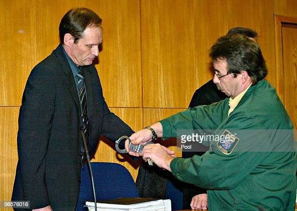 Armin Meiwes gets his handcuffs removed as he attend his retrial on January 12 2006 at the District Court in Frankfurt Germany Meiwes was convicted...