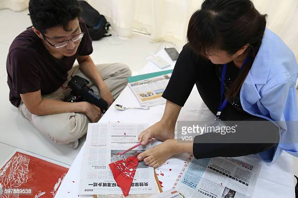Armless girl Xia Hong carves papercutting with her feet during a handcraft competition on August 29 2016 in Beijing China 232 participants attended...