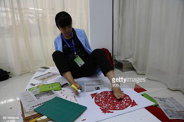 Armless girl Xia Hong fixes her papercutting with glue stick during a handcraft competition on August 29 2016 in Beijing China 232 participants...