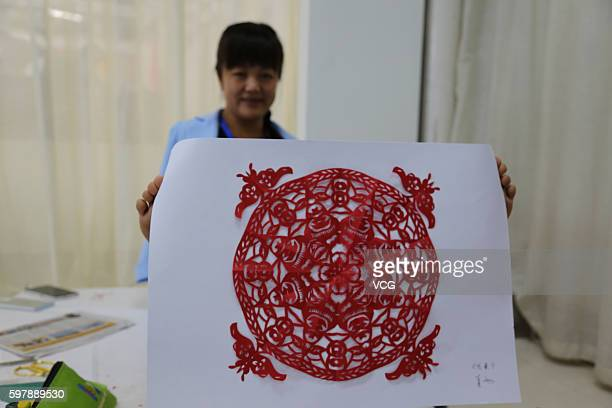 Armless girl Xia Hong shows her artwork of papercutting during a handcraft competition on August 29 2016 in Beijing China 232 participants attended...