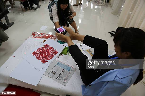 Armless girl Xia Hong takes pictures of herself papercutting with her feet during a handcraft competition on August 29 2016 in Beijing China 232...