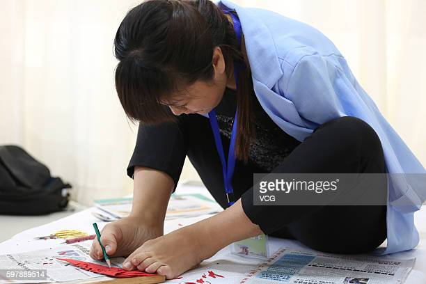 Armless girl Xia Hong traces on red paper with her feet during a handcraft competition on August 29 2016 in Beijing China 232 participants attended...