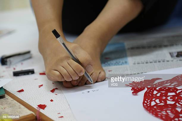 Armless girl Xia Hong writes name of her papercutting 'Harvest' with her feet during a handcraft competition on August 29 2016 in Beijing China 232...