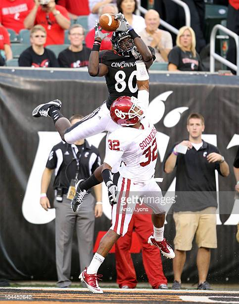 Armon Binns of the Cincinnati Bearcats reaches up for a pass while defended by Jamell Fleming of the Oklahoma Sooners during the game at Paul Brown...