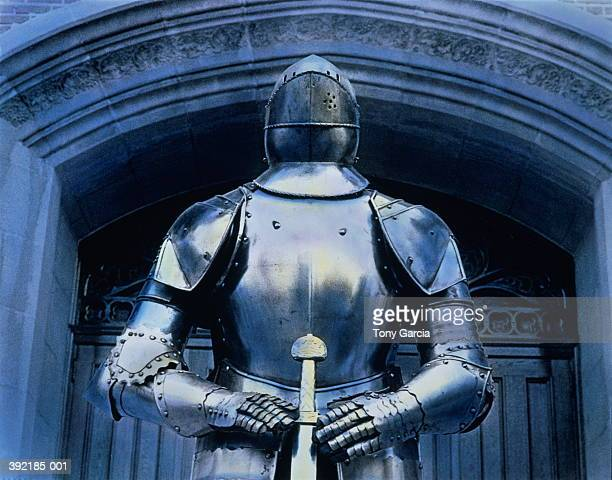 Armor suit standing beneath Gothic archway