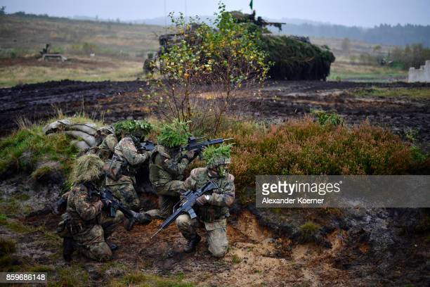 Armored infantryman of the Bundeswehr the German armed forces participate next to a Marder light tank during a simulated attack during military...