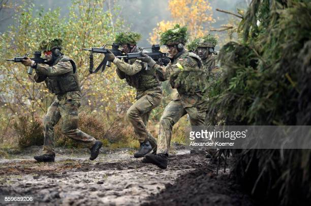 Armored infantryman of the Bundeswehr the German armed forces walk by the Mader light tank during a simulated attack during military exercises on...