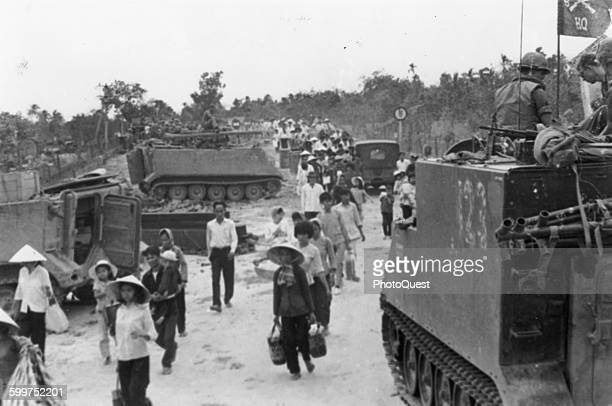 M113 armored personnel carriers stand by as Vietnamese refugees evacuate a village during the Tet Offensive My Tho Viet Nam 1968