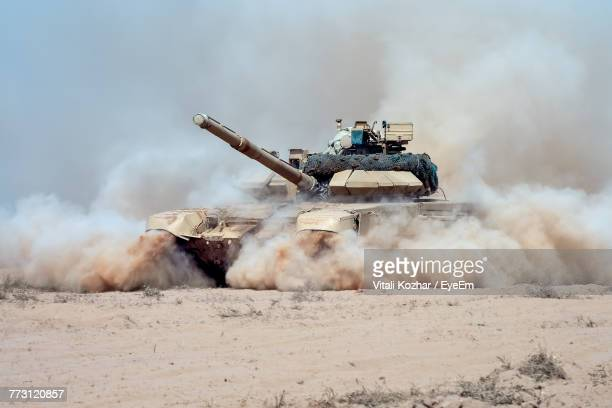armored tank on dirt road against sky - armored tank stock photos and pictures