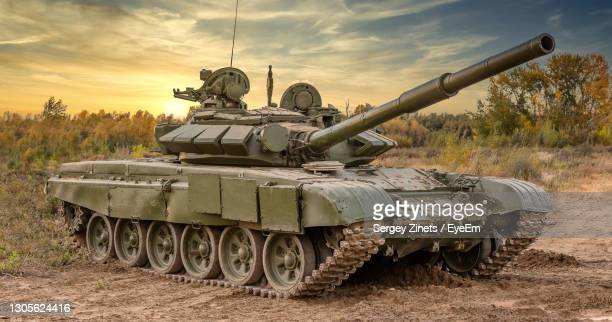 armored tank on field against sky - storage tank stock pictures, royalty-free photos & images