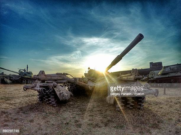 Armored Tanks On Field At Sunset