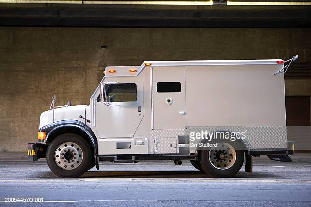 Armored truck on city street, side view