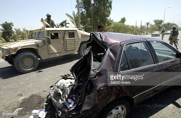 US armored vehicle drives past a damaged car following a car accident on the highway connecting the Iraqi capital do Baghdad International Airport 13...