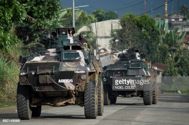 Armoured personnel carriers drive down a village road in Marawi on the southern island of Mindanao on June 4 2017 Efforts to rescue up to 2000...