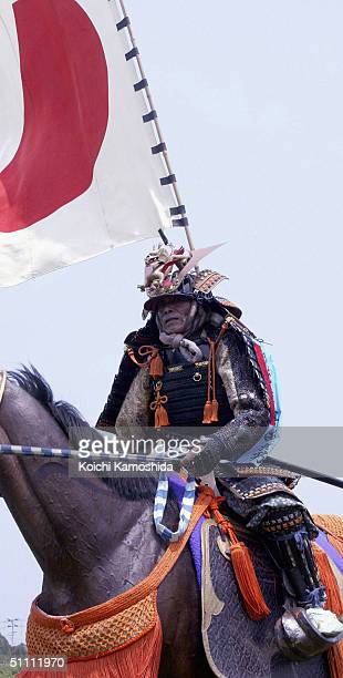 Armoured Samurai horsemen take part in a parade before the ancient horse racing event during the Soma-Nomaoi festival on July 24, 2004 in Haramachi...