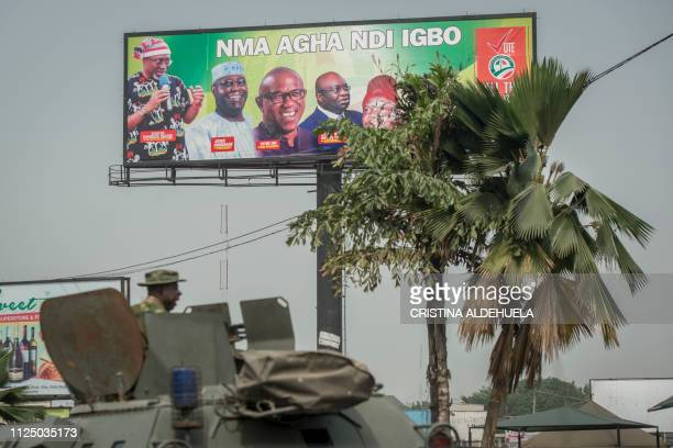 A armoured vahicle passes under a People Democratic Party's billboard in Aba southeastern Nigeria on February 15th 2019 during a military patrol...