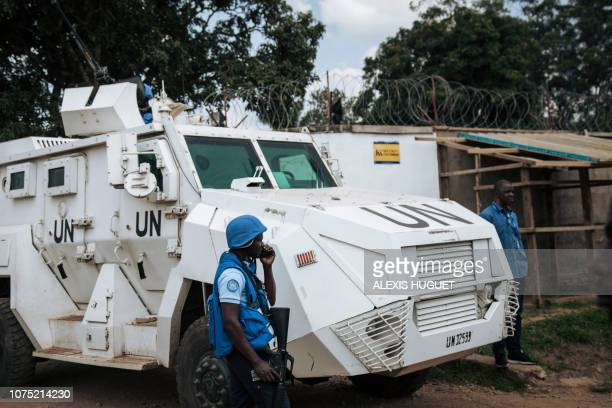A MONUSCO armoured vehicle guards outside the Ebola response headquarters in Beni while protesters demonstrate against the postponement of elections...