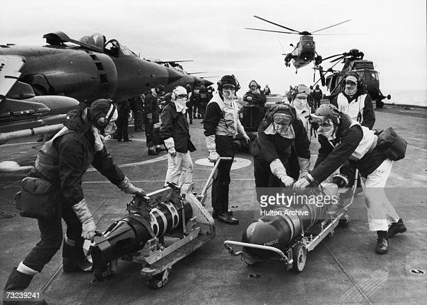 Armourers moving torpedoes on the flight deck of HMS Hermes during the Falklands conflict May 1982 The torpedos are to rearm Sea King helicopters to...