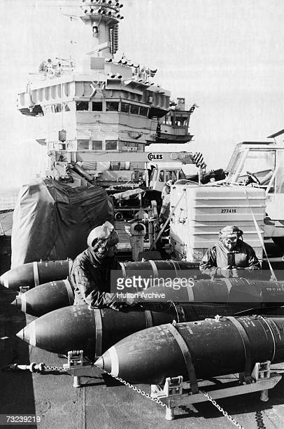 Armourers of the 800 British Naval Air Squadron preparing 1000lb bombs on the flight deck of HMS Hermes during the Falklands conflict May 1982