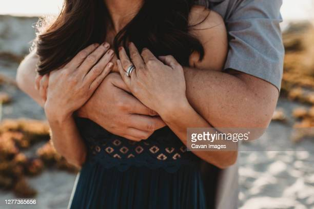 arms and hands detail image of husband embracing wife from behind - short sleeved stock pictures, royalty-free photos & images