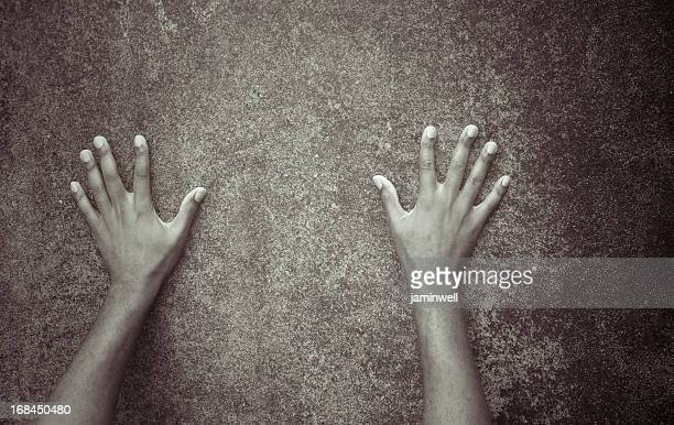 arms and hands spread against dirty grunge wall