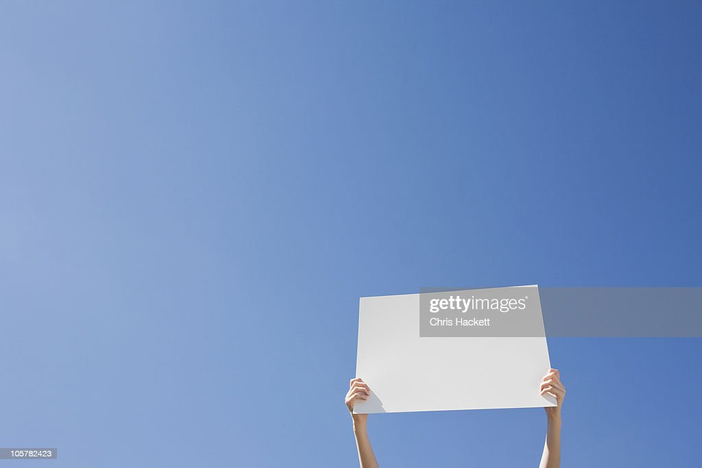 Arms holding a blank placard : Stock Photo