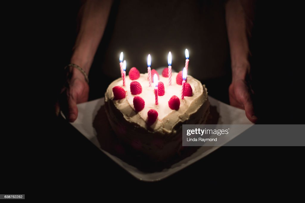 Arms Holding And Showing A Heart Shape Birthday Cake With