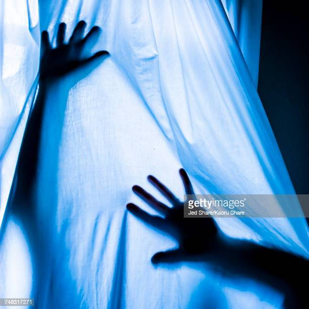 arms of caucasian man pressing against blue curtain - claustrophobia stock photos and pictures