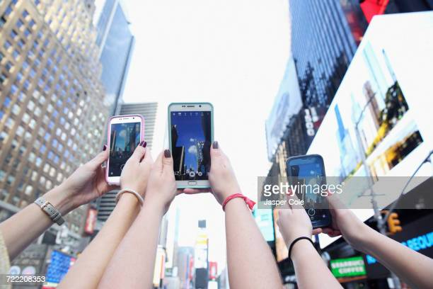 Arms of Caucasian women photographing skyscrapers with cell phones