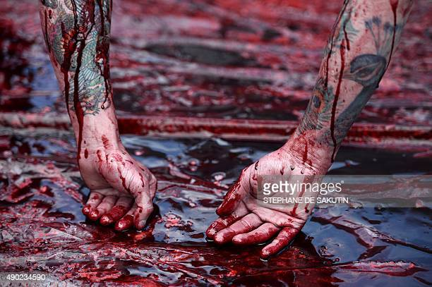 A arms of man covered in red paint to represent blood hangs by his feet as activists of the animal liberation movement 269life stage an open air...