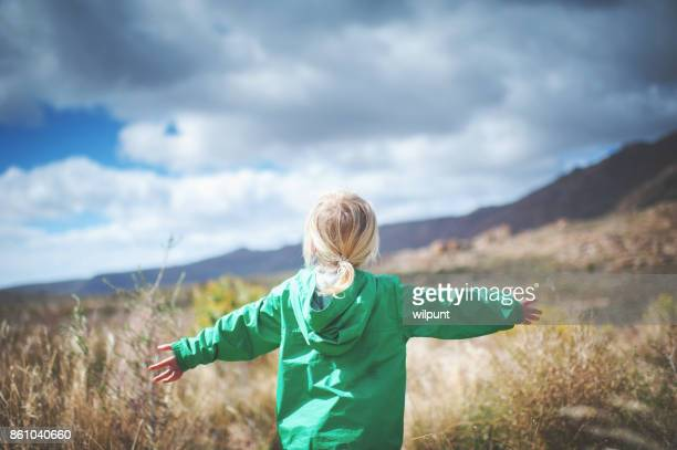 Los brazos levantado a chica naturaleza vista posterior