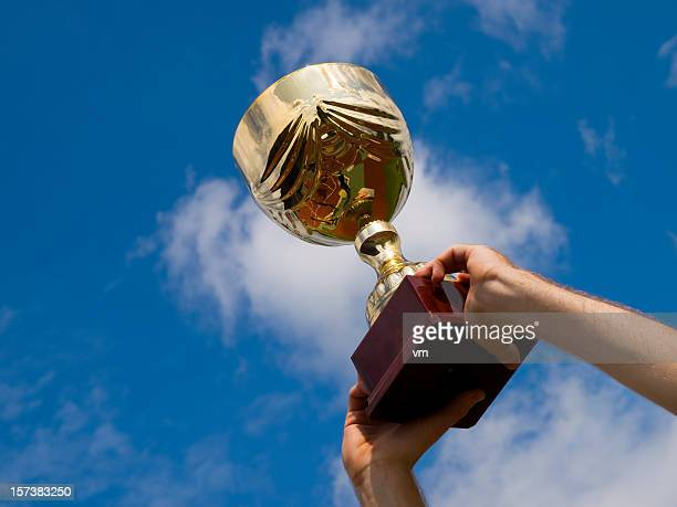 Arms raising the winning trophy