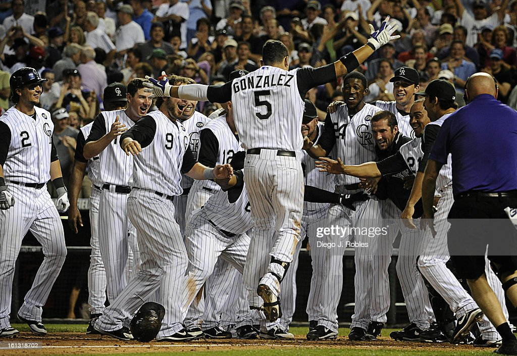 Arms wide open after hitting a walk-off solo home run in the bottom of the 9th inning, Colorado Rockies left-fielder Carlos Gonzalez (5) jumps on home base while his teammates emphatically greet him. The Colorado Rockies beat the Chicago Cubs, 6-5, in Den : News Photo