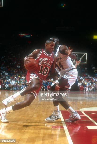 J Armstrong of the Chicago Bulls drives on AJ English of the Washington Bullets during an NBA basketball game circa 1990 at the Capital Centre in...