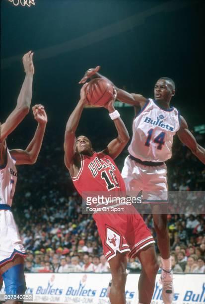 J Armstrong of the Chicago Bulls has his shot blocked by AJ English of the Washington Bullets during an NBA basketball game circa 1990 at the Capital...
