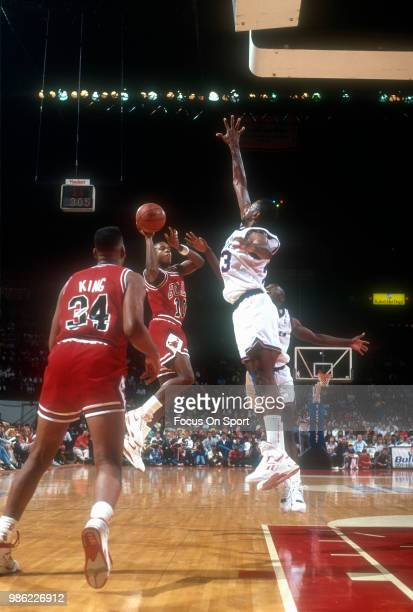 J Armstrong of the Chicago Bulls looks to get his shot off over the outstretched arm of Charles Jones of the Washington Bullets during an NBA...