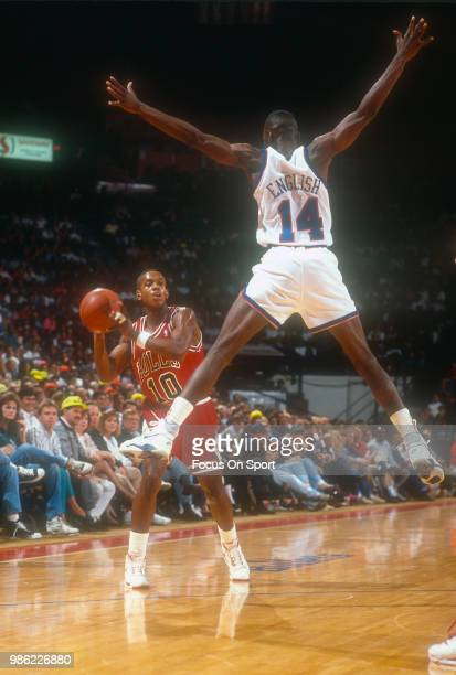 J Armstrong of the Chicago Bulls looks to pass the ball past AJ English of the Washington Bullets during an NBA basketball game circa 1990 at the...