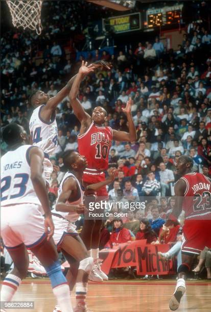 J Armstrong of the Chicago Bulls shoots over Harvey Grant of the Washington Bullets during an NBA basketball game circa 1990 at the Capital Centre in...