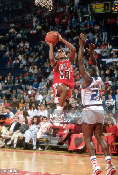 J Armstrong of the Chicago Bulls shoots over Ledall Eackles of the Washington Bullets during an NBA basketball game circa 1990 at the Capital Centre...