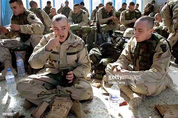 S Army 101st Airborne Division Pvt Thomas Kevin of Belpre Ohio and Pfc John Meck of Susquehanna Pennsylvania eat lunch during their first day at the...